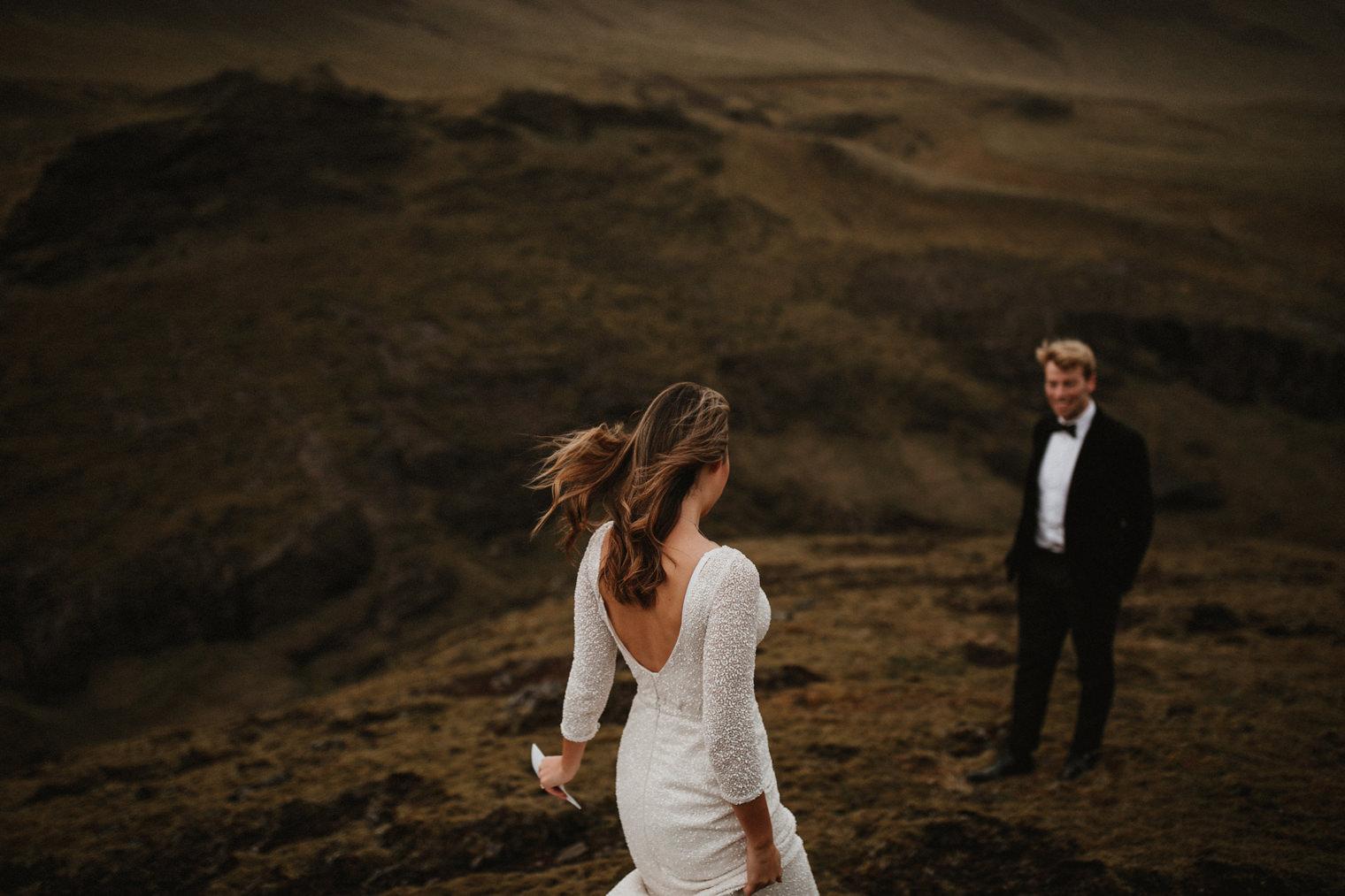 Bride walking towards groom at Iceland wedding in Vik