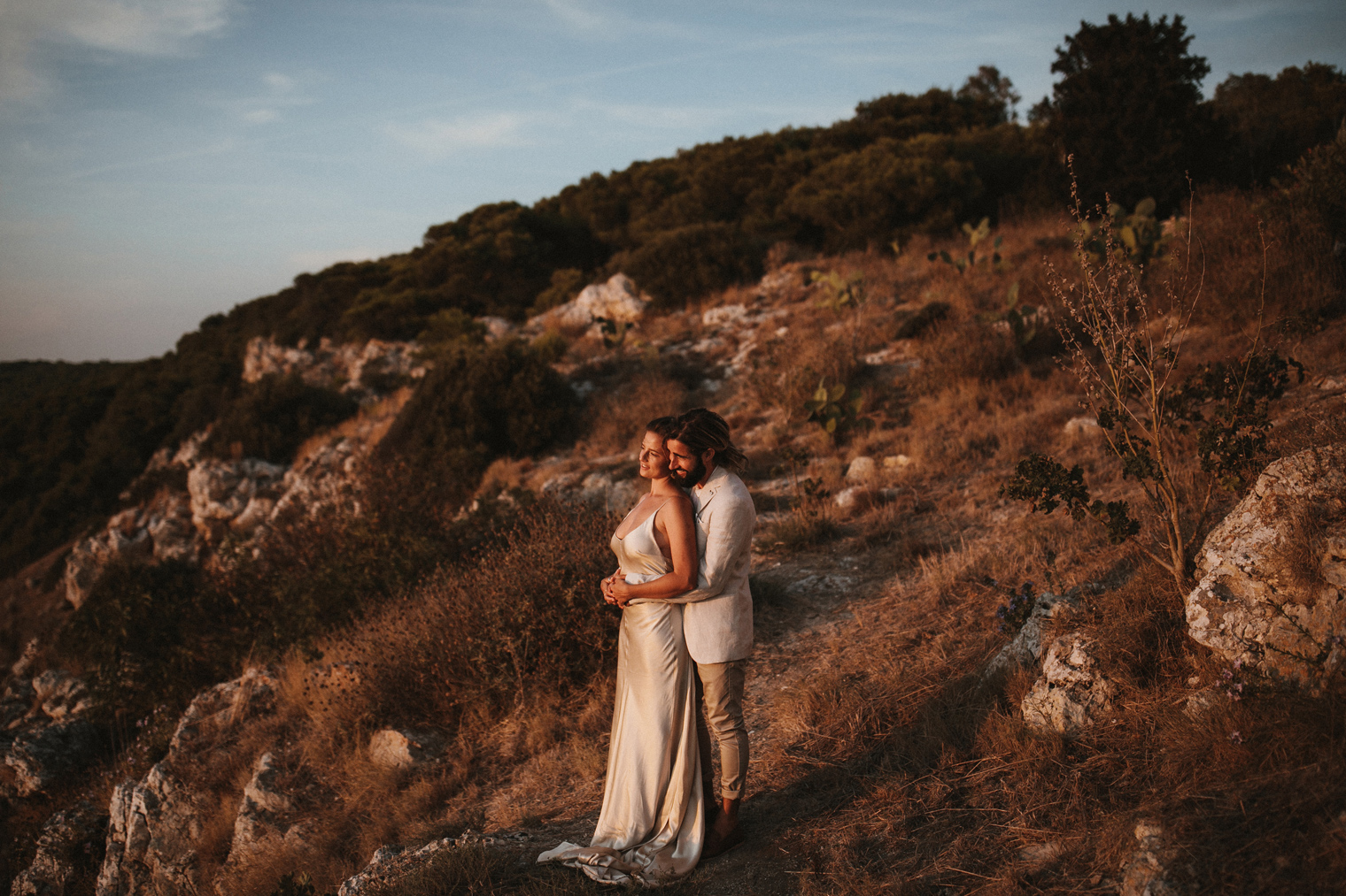 Bride and groom looking out into the sunset after their intimate wedding in Gallipoli