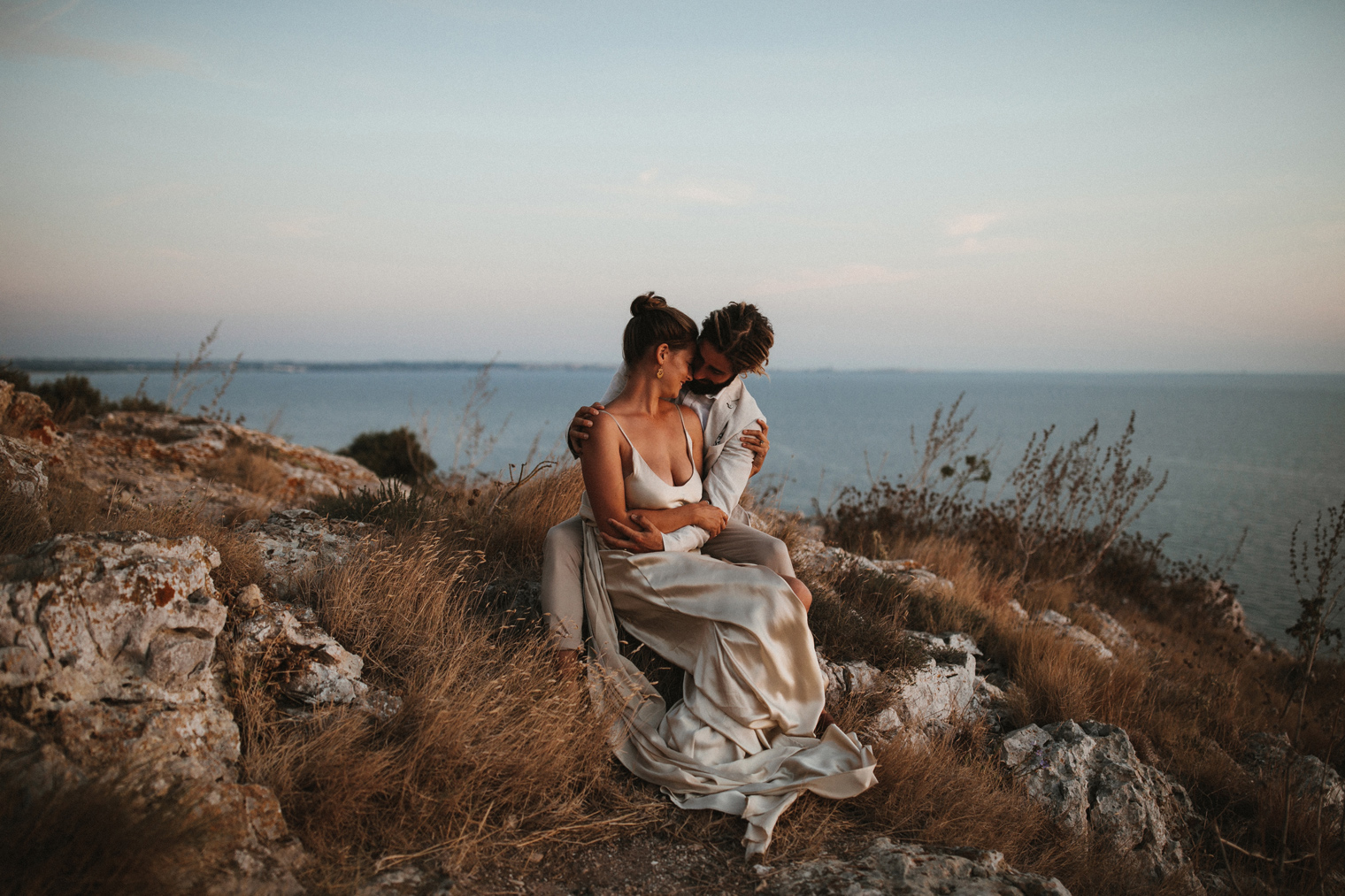 intimate wedding portrait of couple sitting next to the ocean in Puglia after their intimate Italian wedding in Gallipoli
