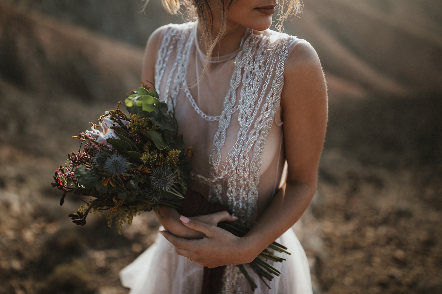 Bride wearing a Marco & Maria Wedding gown while holding dried flower bouquet
