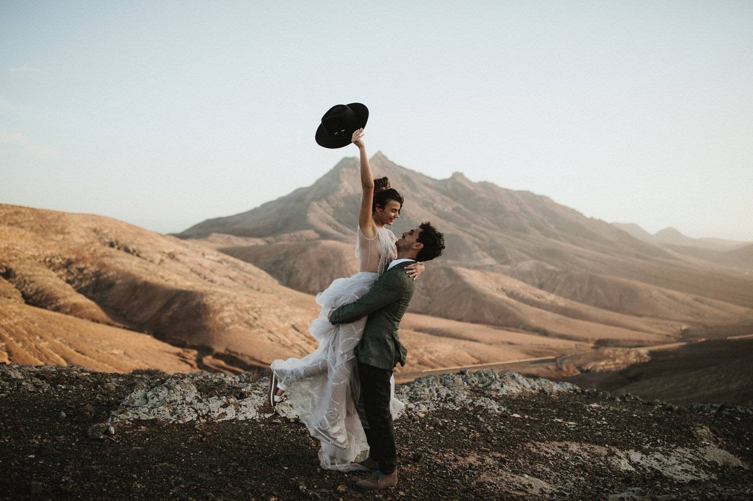 Groom lifting up bride while she waves his hat during Fuerteventura Elopement shoot