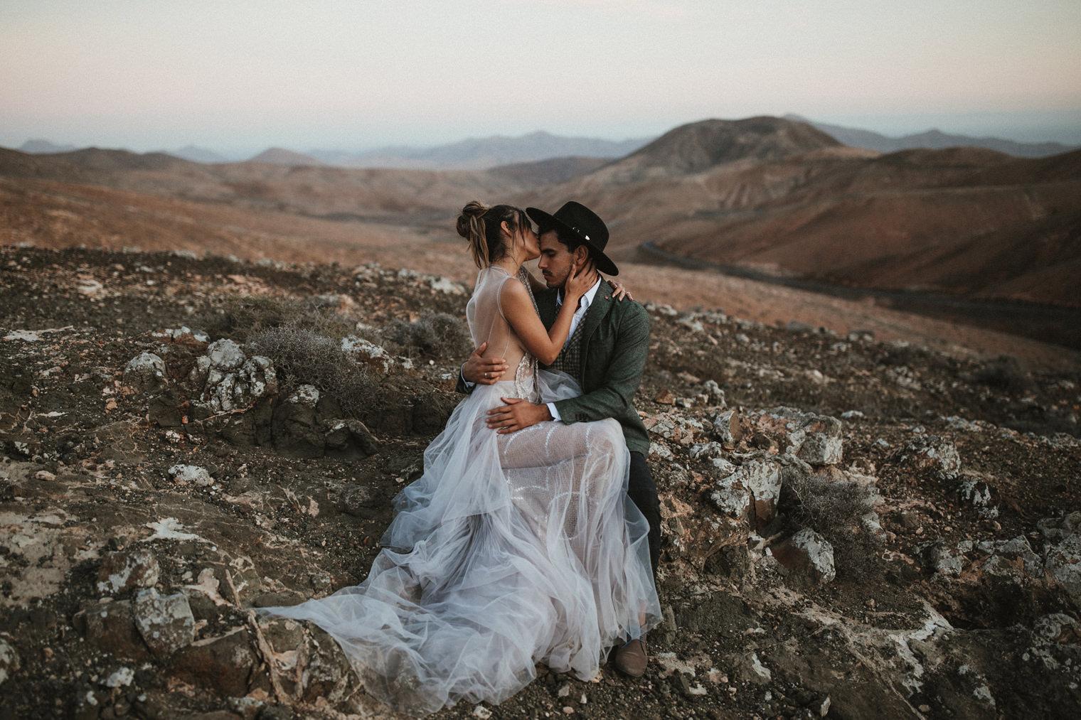 Bride wearing Marco & Maria Wedding Gown sitting on Groom's lap in Fuerteventura