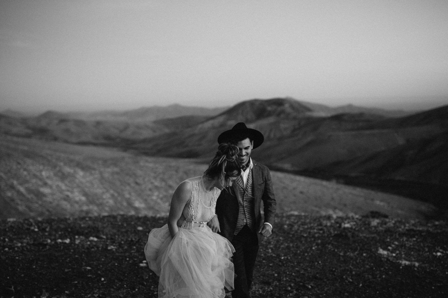 Black and White photo of bride and groom walking and laughing in Fuerteventura