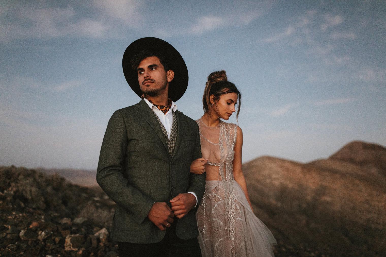 stylish Groom wearing wide brimmed hat during Fuerteventura elopement shoot